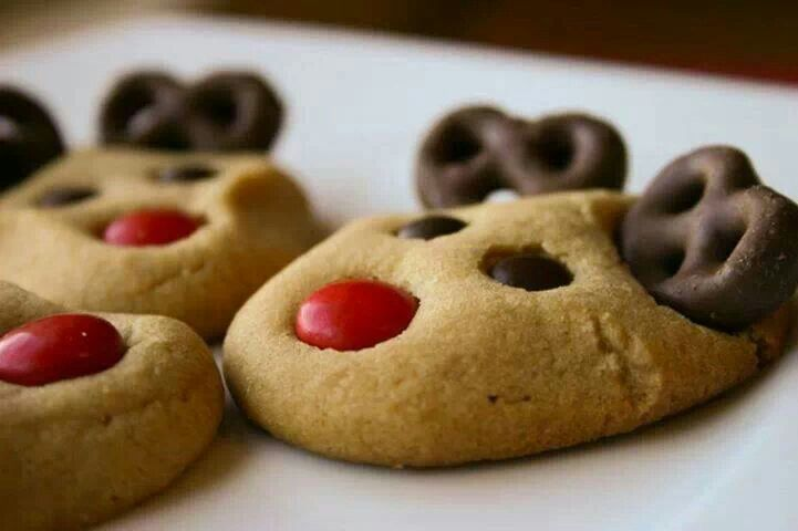 festive reindeer cookies Make peanut butter cookies Use mini brown m&m's for eyes Red m&m for nose and use chocolate covered pretzels from Bulk Barn for ears