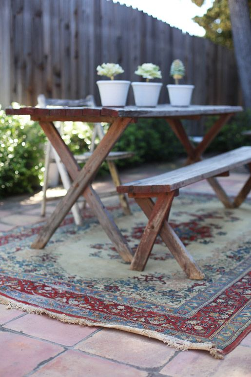 Finding an old oriental rug that is too beat up for the home? Use it under your outside dining table - tres chic