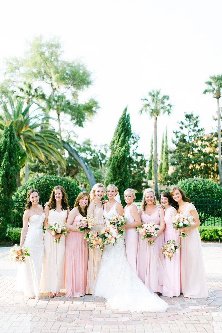 the bride and her bridesmaids at the racquet club reception holding their loose peach, blush and white bouquets of ranunculus, peonies, roses, spirea, tulips and greenery.