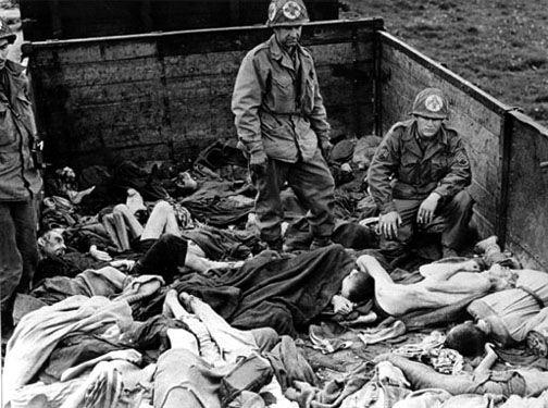 """American soldiers examine the bodies found on the """"death train"""" outside the Dachau camp."""