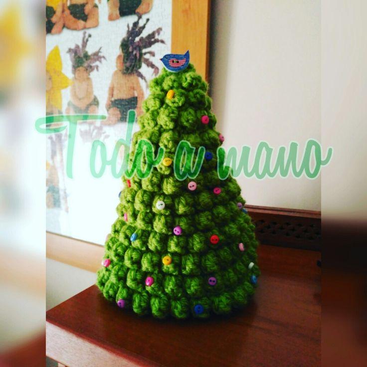 Árbol de Navidad realizado a croché con puntos bajos y Popcorn. Adornos con mini botones y por estrella un pajarito.