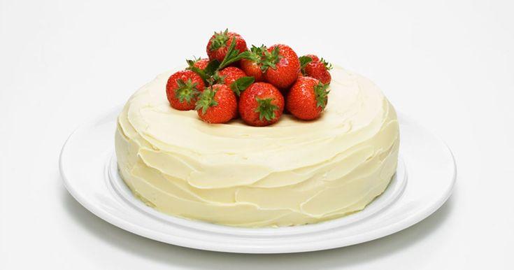 En härlig tårta fylld med jordgubbsmousse och rabarberkompott med kardemumma. Tårtan är glaserad med vit chokladtryffel, både gott och annorlunda.