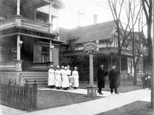Nurses carry a casket from the Gardiner Funeral Home on Kennedy Street in Winnipeg during the flu epidemic of 1918-1919.  Source: Archives of Manitoba, Foote Collection No. 189, N1789.