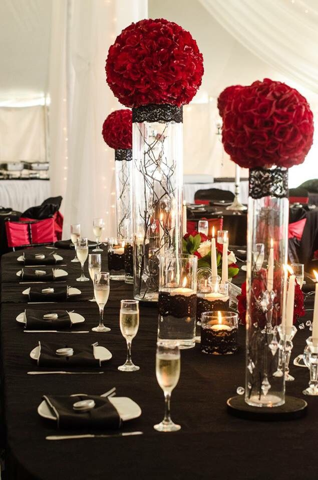 """Deep red rose balls on cylinder vases with hanging crystals and black lace vase wraps with 8"""" LED uplights. Red satin table linen with black lace to the floor overlay. Black polyester dinner napkin. Wedding centerpieces and tabletop decor. Tablescape. Wedding rentals."""