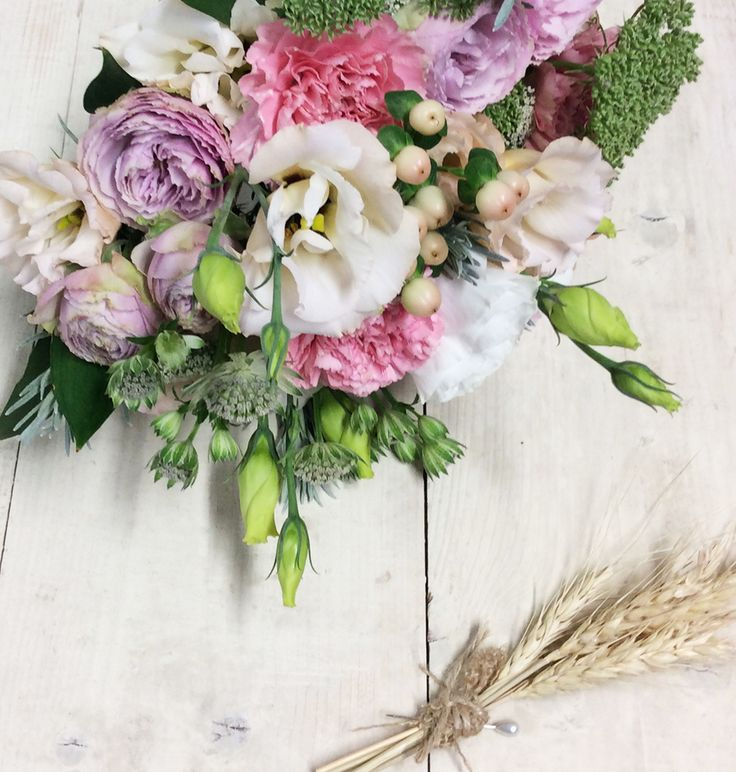 a lovely pastel textured bouquet featuring Lissianthus, Carnation, Hypericum Berries, Queen Annes Lace, with a wheat buttonhole for the groom