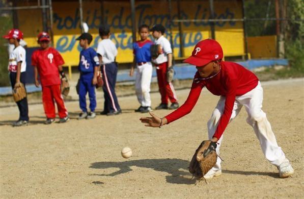 "A boy fields a ball during a baseball practice at the ""23 de Enero"" neighborhood in Caracas March 1, 2011.  REUTERS/Jorge Silva"