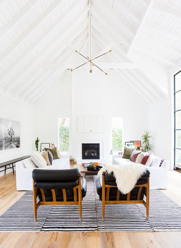 Bright, white, and spacious living room with modern light fixture, leather armchairs, and lots of natural light