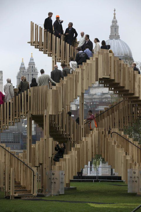 Visitors stand on the steps of an architecture installation entitled 'Endless Stair' outside the Tate Modern art gallery, with St. Paul's Cathedral partially visible in the background at right, during an event to launch the London Design Festival, London, Friday, Sept. 13, 2013. The free standing temporary installation was designed by dRMM Architects and constructed from American tulipwood. (AP Photo/Sang Tan)
