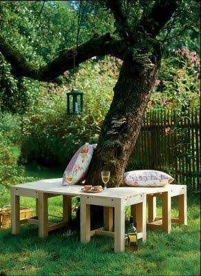 Bancos de madeira rústica ao redor da árvore. luminária pendurada