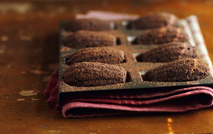 Медово-шоколадные мадлен 140 г сливочного масла 40 г темного шоколада (70%) 2 яйца 1 ч.л. ванильного экстракта 90 г мелкого сахара 40 г жидкого меда 140 г муки 1 ч.л. разрыхлителя 20 г несладкого какао-порошка какао-порошок для посыпки