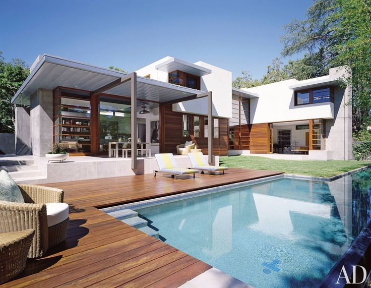 A Palo Alto, California, pool terrace features rich wood decking and a modern outdoor dining area.
