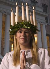 "Sankta Lucia December 13th Sweden ""Lux"" Light-Families celebrate at home. The eldest daughter dresses in a long white gown with a red ribbon tied at the waist. She dons a crown of fresh greens &lit candles on her head. attended by younger siblings, girls (attendants) in white robes with tinsel around their waists & heads& boys (starboys) in white robes, cone hats & carrying stars. serve coffee& Lussekatter (Lucia buns) to all people in the house while singing traditional Swedish Lucia songs."