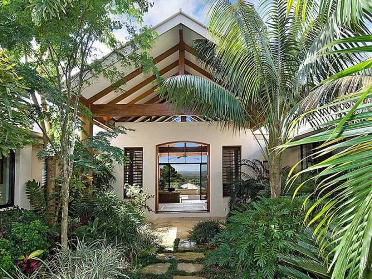 Tropical plants frame this lush outdoor garden which encourages the eye to follow right through the house into the backyard. I love this effect!