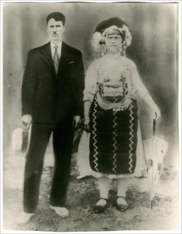 Νυφιάτικη ενδυμασία  από το Ρουμλούκι, που τη συνοδεύει η ομπρέλα ως αξεσουάρ.  Ημερομηνία Έκδοσης: 1930.  Συλλογή Χρυσάνθης Κωστοπούλου;Λουτρός (Ημαθία).  Δημόσια Κεντρική Βιβλιοθήκη της Βέροιας