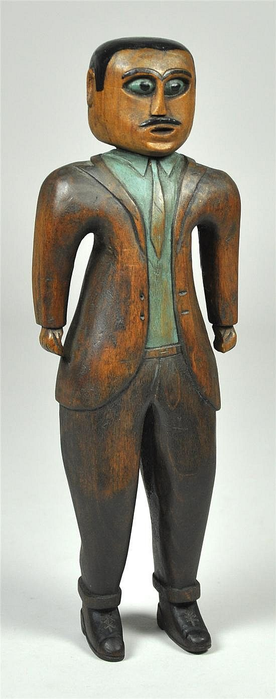 """Carved Southern Folk Art Figure """"Man in Suit"""" Undated. Carved by Charles H. Saunders (1901-1984). Carved face and head, green eyes and pencil mustache; green shirt, stained and painted finish to suit, laced shoes. 10 1/2"""" x 3 1/2"""" x 2"""".  $5175, Ken Farmer Auctions, 06-13-2010."""