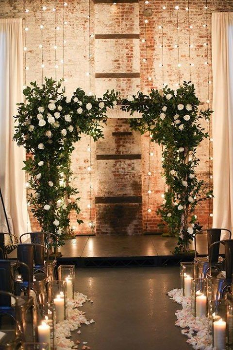 wedding arch with lights in background and candles along aisle