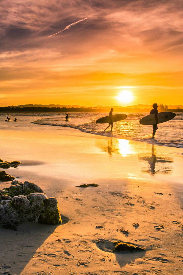Surfers at sunset at the beautiful Byron Bay, Australia ++