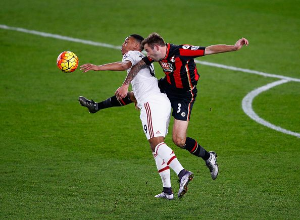 Steve Cook of Bournemouth heads the ball away from Anthony Martial of Manchester United during the Barclays Premier League match between AFC...