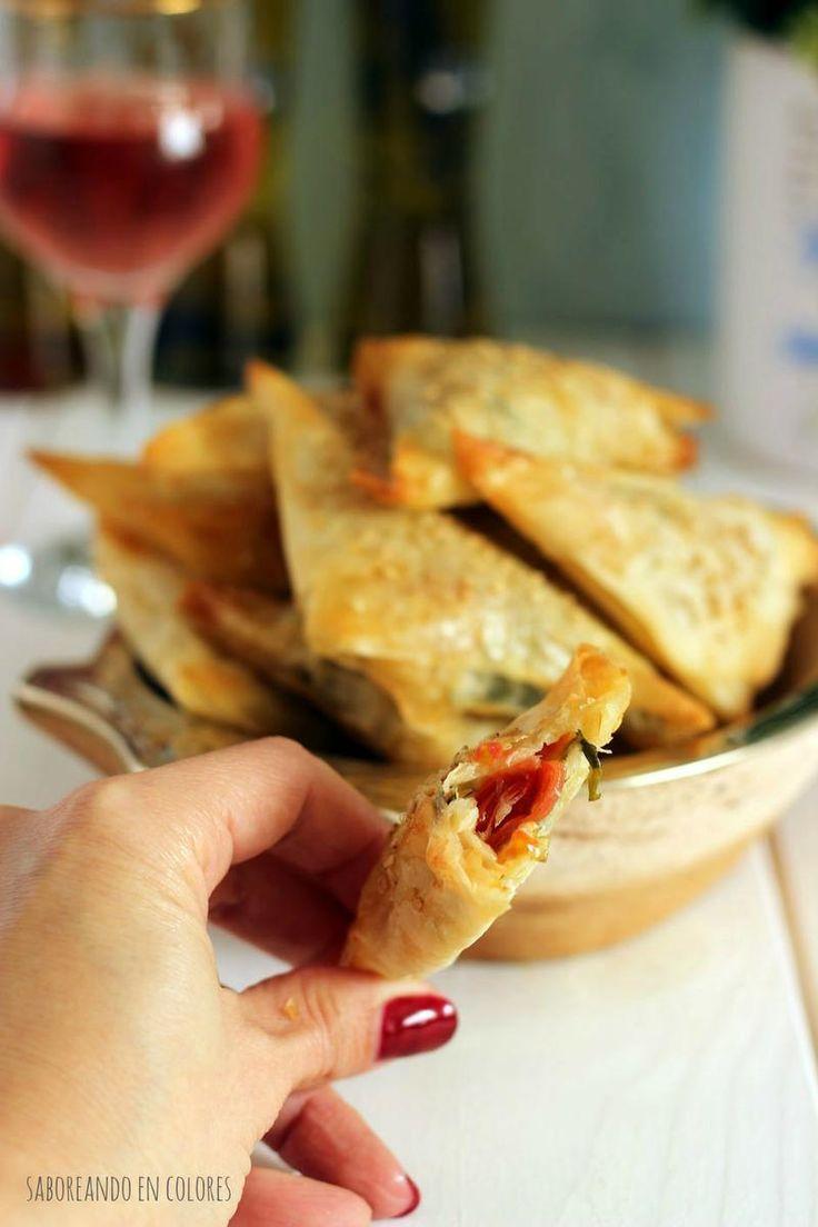 triangulos provolone3 Ingredientes  - Masa filo (8 láminas) / Pasta brick  - Clara de huevo, para pincelar la masa  - semillas de sésamo para decorar (opcional)  Para el relleno  - 2 cdas. de aceite de oliva  - 3 dientes de ajo  - 3 tazas de rúcula fresca picada  - 200 g de tomates cherry (o tomates perita troceados)  - 2 cdas. de albahaca fresca picada  - 100 g de queso provolone rallado  - sal y pimienta a gusto