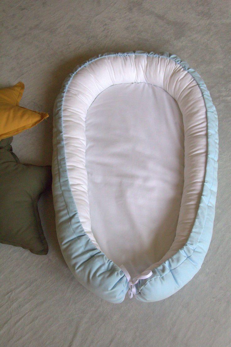Kokon niemowlęcy błękitny.  Kokon przypomina rożek  otula niemowlę i ogranicza mu przestrzeń, co sprawia,że dziecko czuje się bezpiecznie, jak w brzuszku u mamy.  W ciągu dnia kokon niemowlęcy można wykorzystać wszędzie tam gdzie w danym momencie przebywamy, może posłużyć jako wkład do Kosza Mojżesza, łóżeczka czy wózka. Jest to również świetne rozwiązanie dla rodziców śpiących ze swoim maluszkiem. Niemowlę może swobodnie układać w nim nóżki.