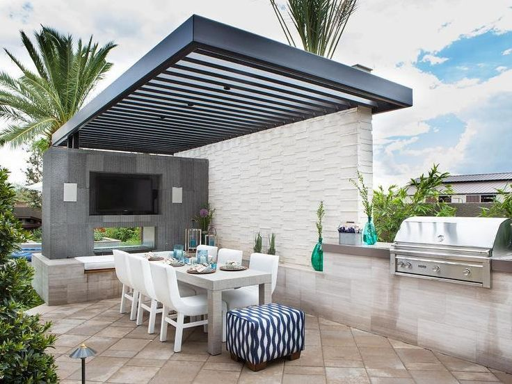 Property Brothers - Contemporary patio features a black pergola providing shade to a concrete parsons dining table lined with modern white dining chairs flanked by a double sided fireplace with flat panel tv which opens to an in ground pool to the left and an integrated bbq to the right.