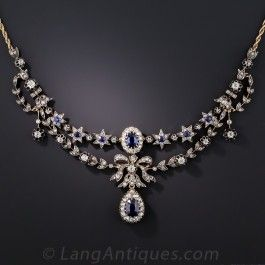 Dating back to the middle-of-the-nineteenth-century, this majestic Victorian necklace, hand-fabricated in silver over gold, highlights a pair of royal blue faceted sapphires, the largest of which (weighing 1.81 cts.) is accompanied by a gemological report from the AGL stating: Natural-No Heat, Pailin (Cambodian) origin. The two primary gemstones glisten and glow from within classic diamond halo settings separated by an extravagant diamond bow. Swags and garlands of sapphire centered stars…
