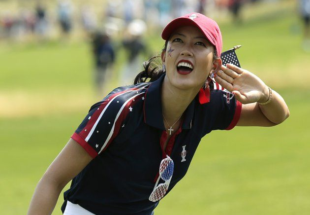 United States' Michelle Wie encourages the crowd along the 15th fairway during a foursome match in the Solheim Cup golf tournament, Friday, Aug. 16, 2013, in Parker, Colo.