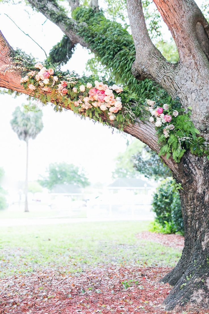 the outdoor reception site at a historic florida home is highlighted by an ancient oak tree adorned with pink, peach and white garden roses, peonies, stock and spirea branches amid the live resurrection fern.