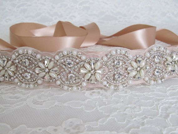 Luxurious bridal sash adorned with pearls, crystals and rhinestones. Securely fastened onto a quality champagne double faced satin ribbon which ties into a bow and drapes down the back of your wedding dress. Perfect finishing touch for your wedding attire!  Please make your choice of beaded trim length and ribbon colour from the drop down menu. Contact me if you have a custom length requirement.  Beaded trim measures 1.75 (4.5 cm) wide.  Ribbon measures 1.5 (3.81 cm) wide and 98 (2.50 m)…