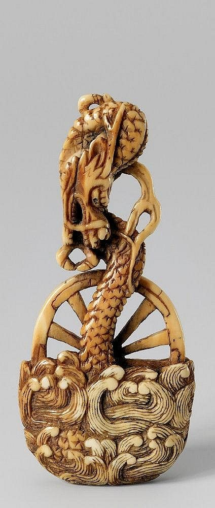An unusual ivory netsuke of a dragon.18th century.  Rising from waves and towering above a chariot wheel riding on billowing waves. The hub of black horn.