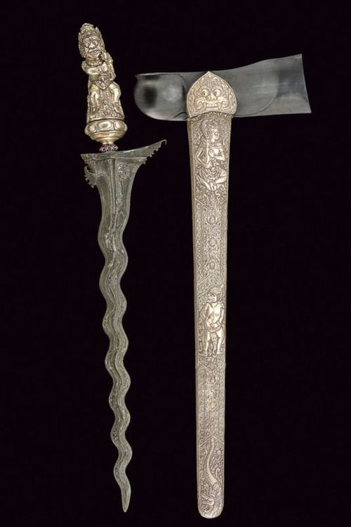 Silver mounted Kris Dagger Dated: 20th century Provenance: Bali Measurements: overall length 56.7 cm The dagger has an undulated, double-edged blade of fine pamor, ribbed at the centre, featuring short grooves at the forte and chiselled curls at the base. The silver mendak features red stone cabochons. The dagger has a silver selut and a silver grip shaped as an in the round, crowned demon, enriched with floral decorations.