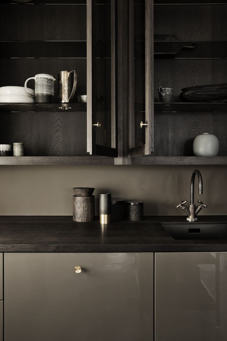 Warm browns with subtle brass door handles and home accessories