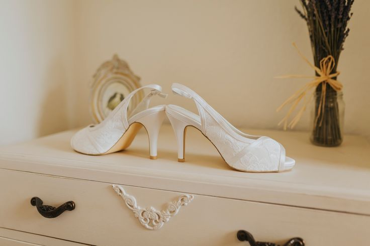 Pretty lace peep-toe bridal shoes. Photo by Benjamin Stuart Photography #weddingphotography #bridalshoes #laceshoes #weddingday #bride #whiteshoes