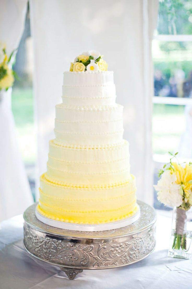 tall yellow ombre wedding cake topped with flowers