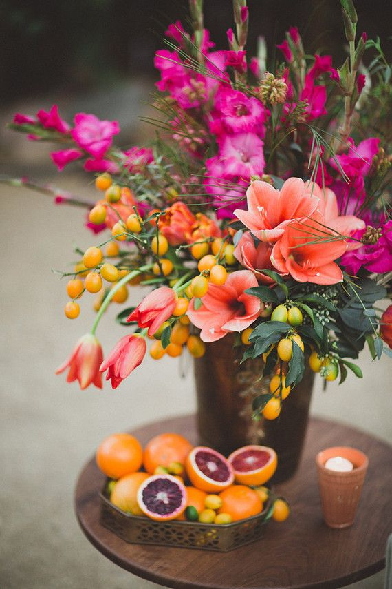 Bright floral centerpiece. Add white and more greenery. Less orange. Change bloody oranges to plums, grapes and a bit of lemons.