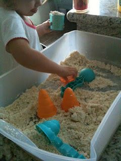 All you need is 5 cups of regular flour and 1 cup of baby oil. Simply mix the two together and it turns into this silky soft sand. You can throw some sand toys into your tray or you can use items such as spoons and measuring cups