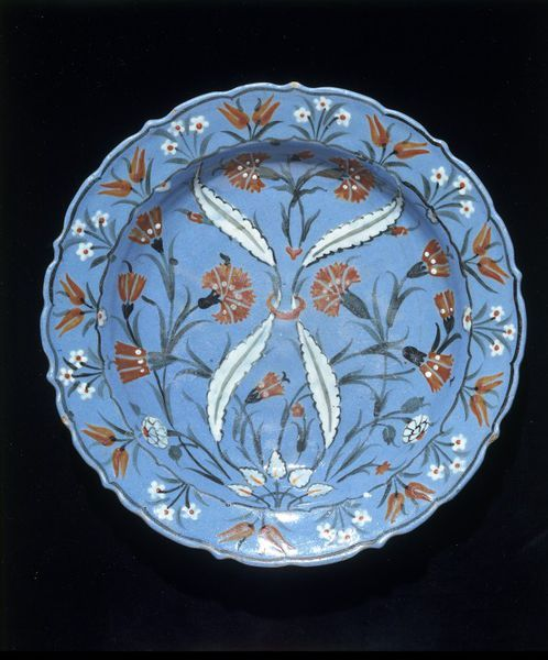Dish | Iznik, Turkey, ca. 1560-1565 | Fritware, covered in pale blue slip, polychrome underglaze painted, glazed | This decorative dish has the coloured ground that featured on some Iznik wares from the 1550s. At this time potters in Iznik in Turkey were using a variety of coloured slips (liquid clay) to cover the bodies of their wares. They then added detailed designs in slips of contrasting colours and paint | VA Museum, London