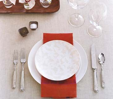 For an eye-catching place setting, rest a bold colored napkin in between stacked white dinner and salad plates.
