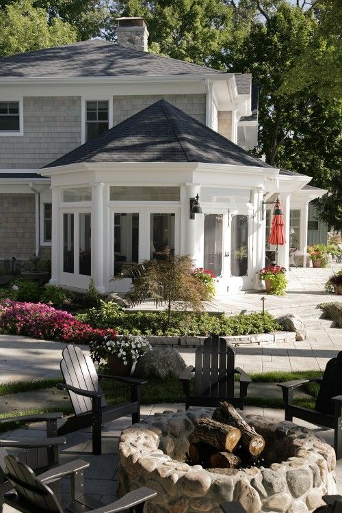 a circular fire pit surrounded by dark gray adirondack chairs echo the architecture of this home