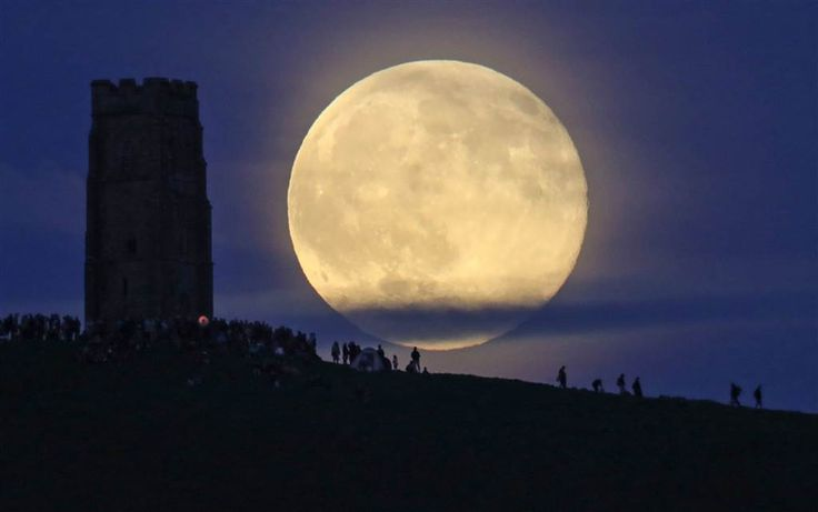 "A full ""strawberry"" moon rises behind Glastonbury Tor as people gather to celebrate the summer solstice on June 20 in Somerset, England. The ""strawberry"" moon is the name given to a full moon in June by Native Americans because it marks the beginning of strawberry picking season"