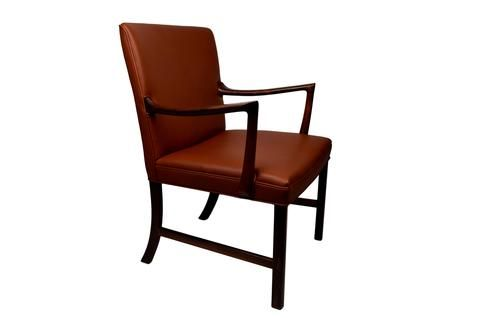 A rosewood armchair upholstered with brown aniline leather by Ole Wanscher