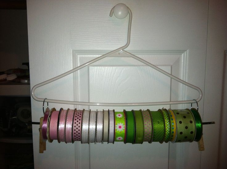 DIY ribbon holder. You will need: one hanger, cheap shower curtain clips ($1.57 for 12 at Wal-Mart), dowel rod and springy clothes pins. Clip the shower curtain hooks onto the hanger, run the dowel rod through the spool on the ribbon and then through the shower curtain hooks. Clip the clothes pin onto the dowel rod to hold all of it in place. How easy is that???
