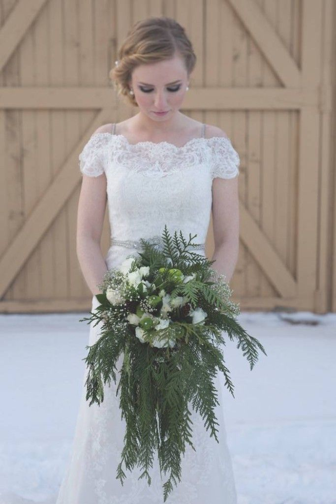 A winter bride with a white wedding bouquet http://calgarybride.ca/cb-blog/real-weddings-engagements/amanda-and-jeffs-navy-and-gold-rustic-winter-wedding/