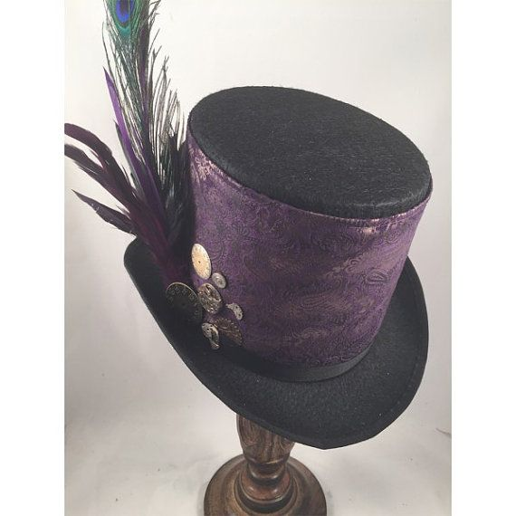STEAMPUNK TOP HAT Steampunk Mens Top Hat with Plum Paisley Print Band. This style comes in a black Felt Tall Top Hat with plum paisley print band, purple feathers and clock parts. A very classy stunning hat. Crown 6, Brim 2 1/2, Diameter 9 1/2, Front to Back 11 3/4 All my Steampunk hats are made with real clock and watch parts making each ha t a unique work of art. Each hat is hand made with real parts and may vary slightly from image shown. SIZING: M 22 - 22 1/2 L. 22 3/4 -23 Please ch...