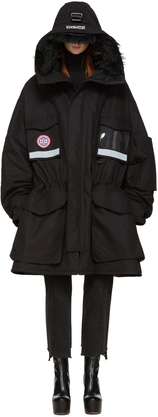 Long sleeve down-filled parka in black. Oversized fit. Cinch strap at crown of hood. Detachable faux-fur trim and logo embroidered in white at brim of hood. Drawstring fastening at hood. Concealed zip closure featuring Velcro placket at front. Flap, zippered, and patch pockets at body. Embroidered logo patch and clear vinyl trim at front. Reflective bands in grey at front and back. Inset rib knit cuffs. Zippered vent at side seams. Patch pocket with Velcro fastening and waist drawstring at…