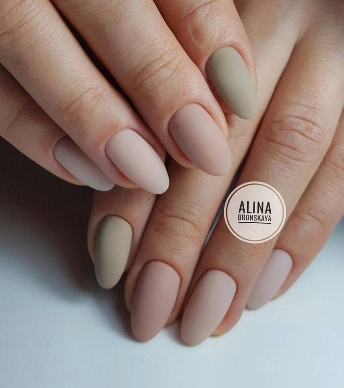 shades pf pastel pink, and grey matte nail polish, on the oval manicure of two h…