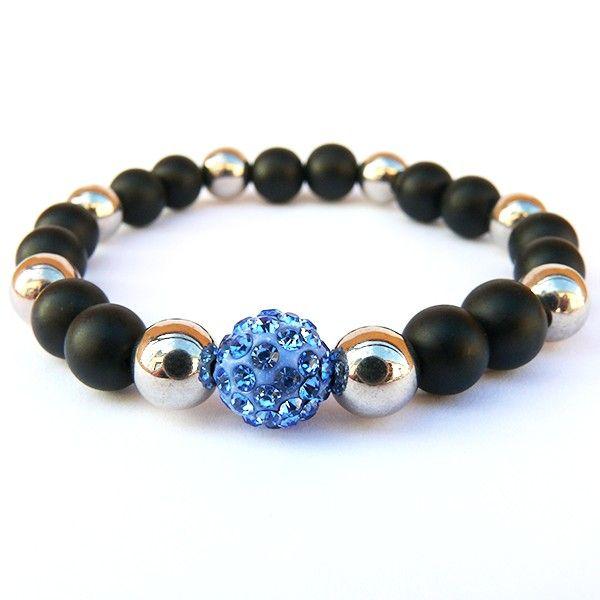 Náramek je vyrobený z černých matných skleněných korálků doplněný o stříbrné akrylové korálky. Dominantní korálek je modrý shamballa korálek s kamínky. Korálky jsou navlečené na lycru, která je elastická a usnadňuje navlečení i svlečení z ruky.