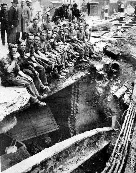 Royal Engineers sit and drink their tea on the edge of a bomb crater in the middle of London 21 October 1940.