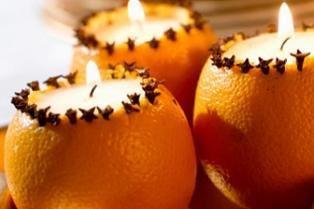Corte uma tampa na parte de cima da laranja (média 3cm, mesmo diâmetro das velas com base de alumínio), retire a laranja usando uma faca para soltá-la da casca e depois retire com a ajuda de uma colher). Preencha a casca vazia com arroz, dando suporte à vela. Para caprichar no visual, espete cravos por toda a volta.