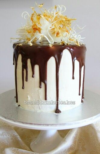 Butter cake with layers of cream, covered in buttercream icing with a drizzle of chocolate ganache, decorated with toffee, white chocolate and gold leaf!